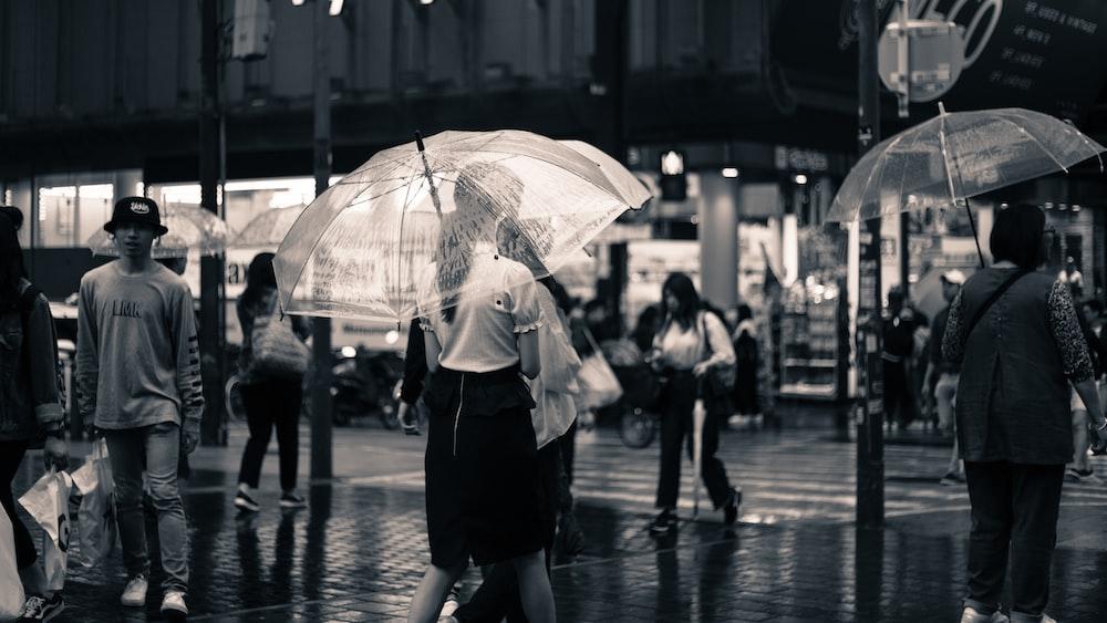 grayscale photo of woman walking using umbrella