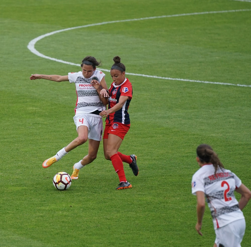 women playing soccer on field