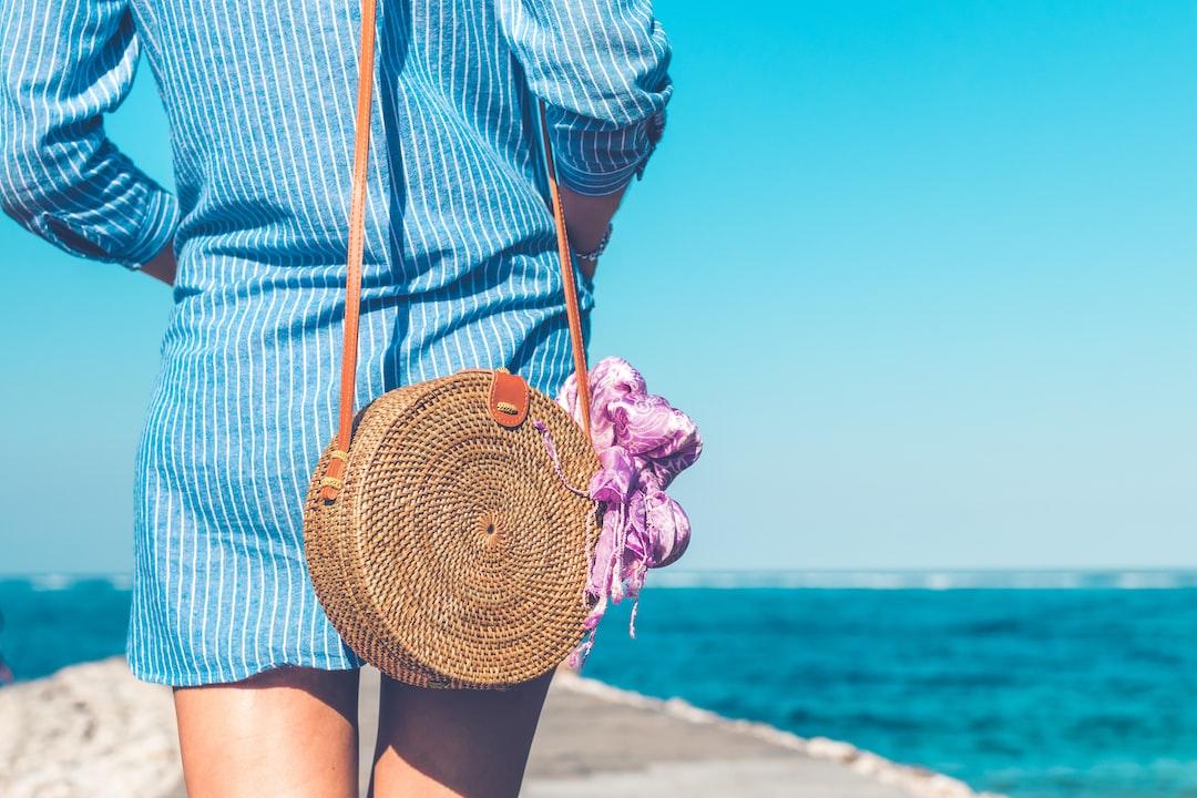 Woman with fashionable stylish rattan bag outside.