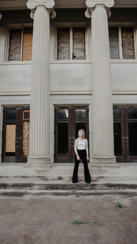 woman standing near gray column