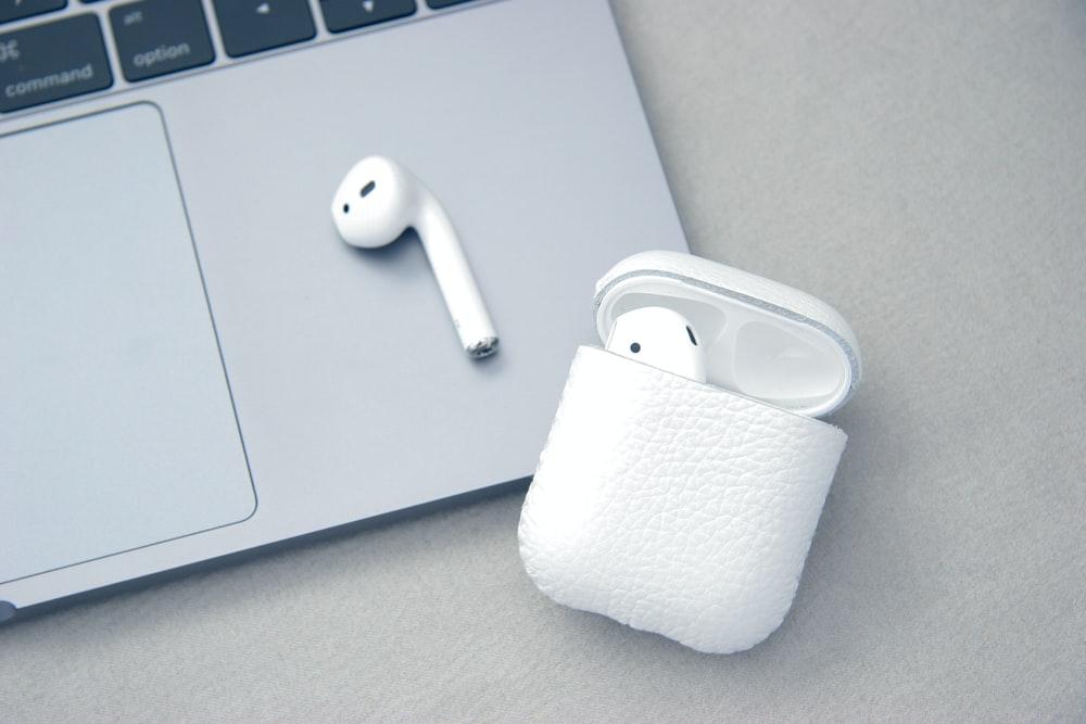 white Apple AirPods beside MacBook Pro