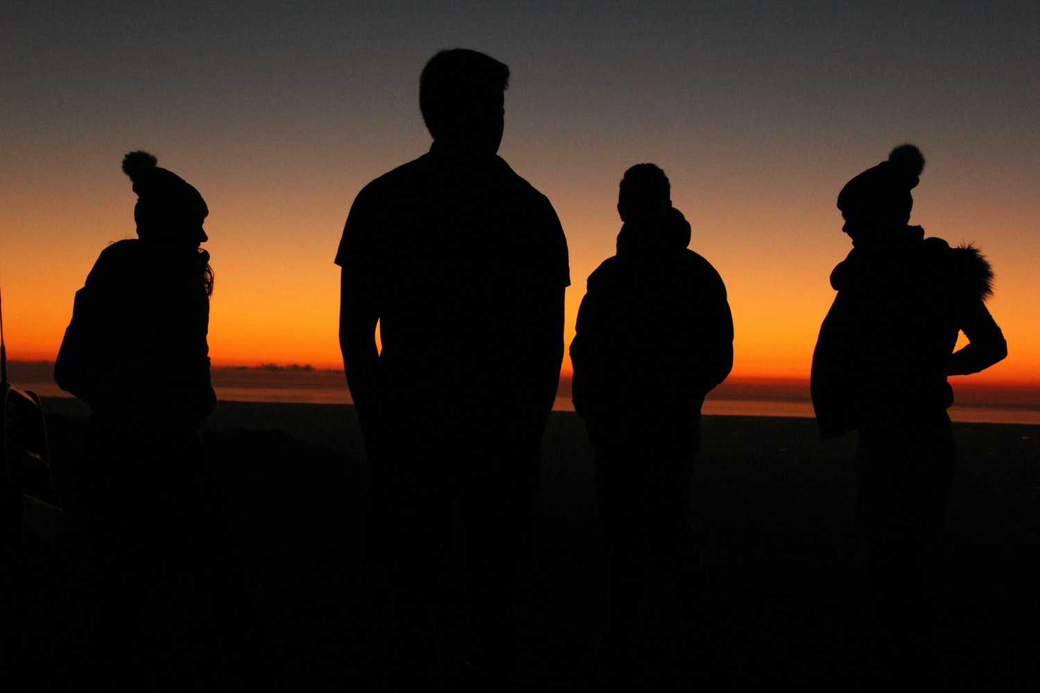 silhouette of four persons standing during sunset