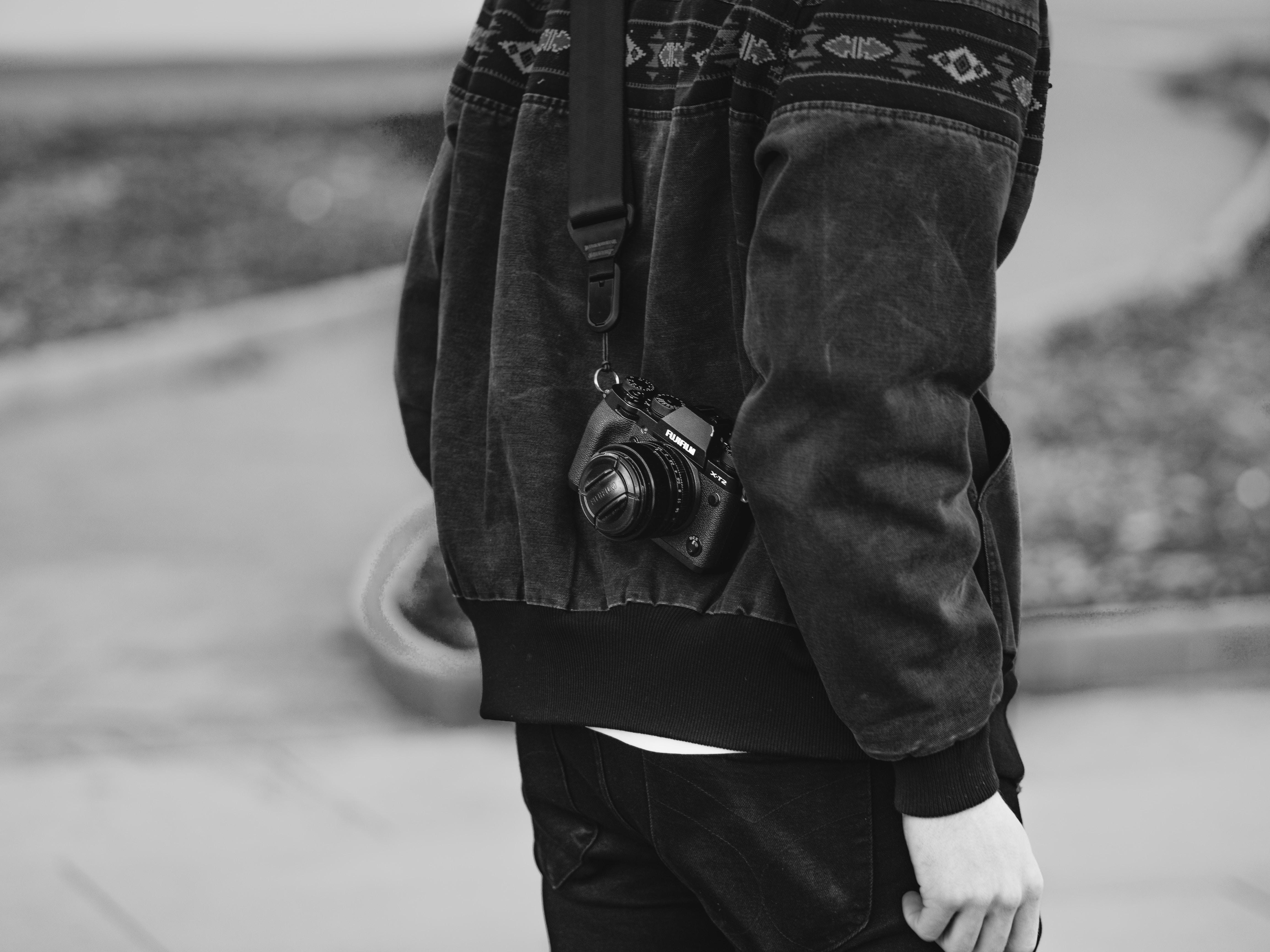 man carrying black DSLR camera