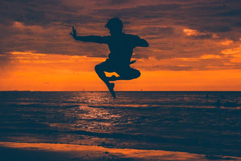 silhouette of man jump on seashore