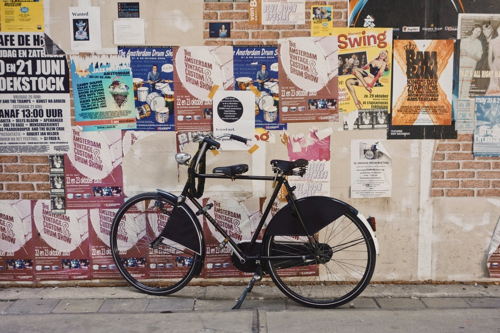 black bicycle parked beside a wall full of poster