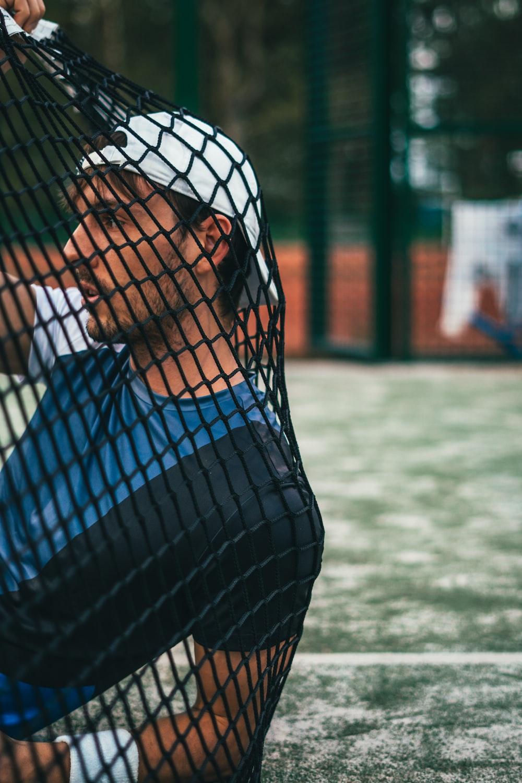 man leaning on black net