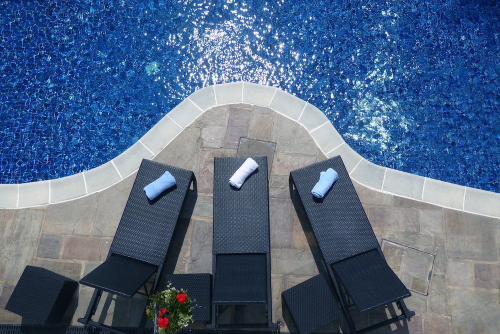three black sunloungers beside swimming pool