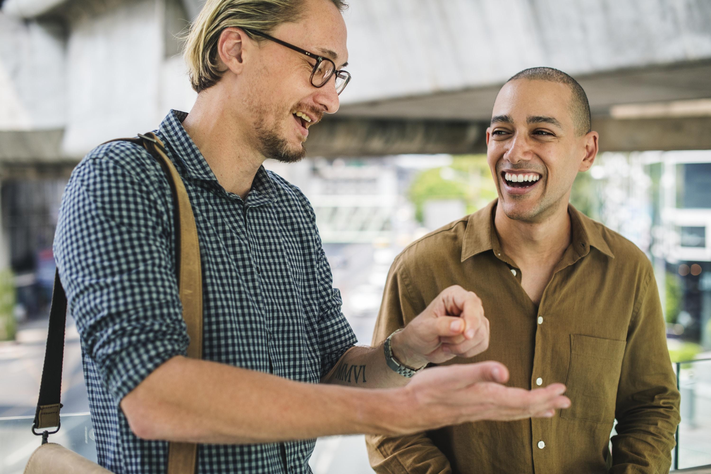 two men having conversation while walking