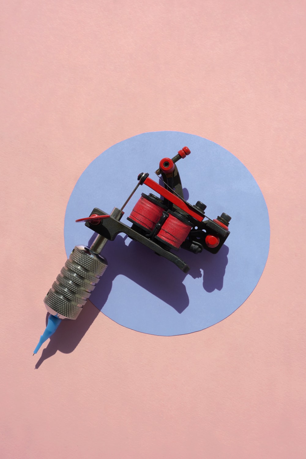 black and red tattoo machine on pink surface