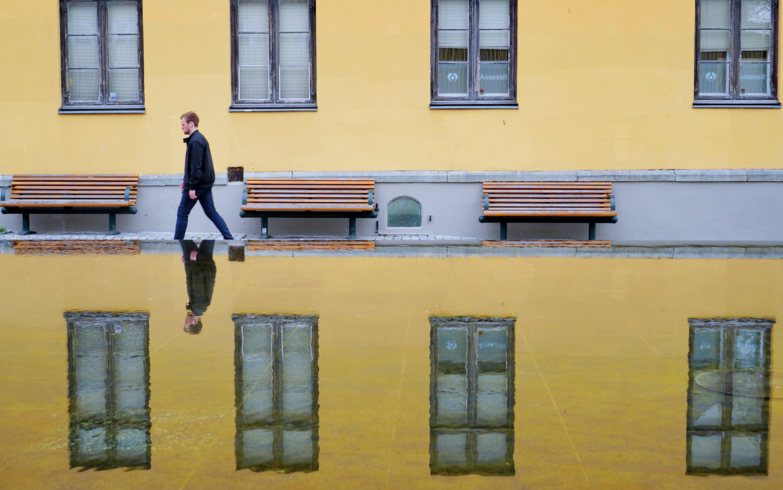 mirror photography of man waking on street