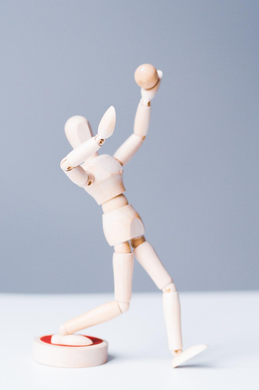 brown manikin figure on white surface