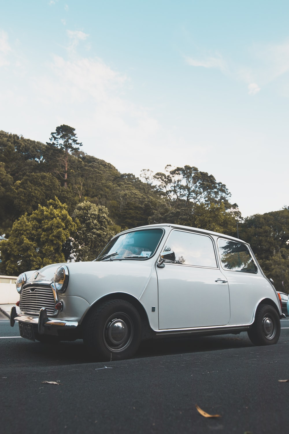 white classic car travelling on the road