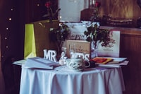 two red roses and mr. & mrs. free-standing letters on top of table