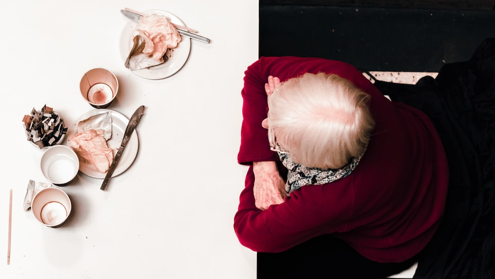 woman resting her hand on white table