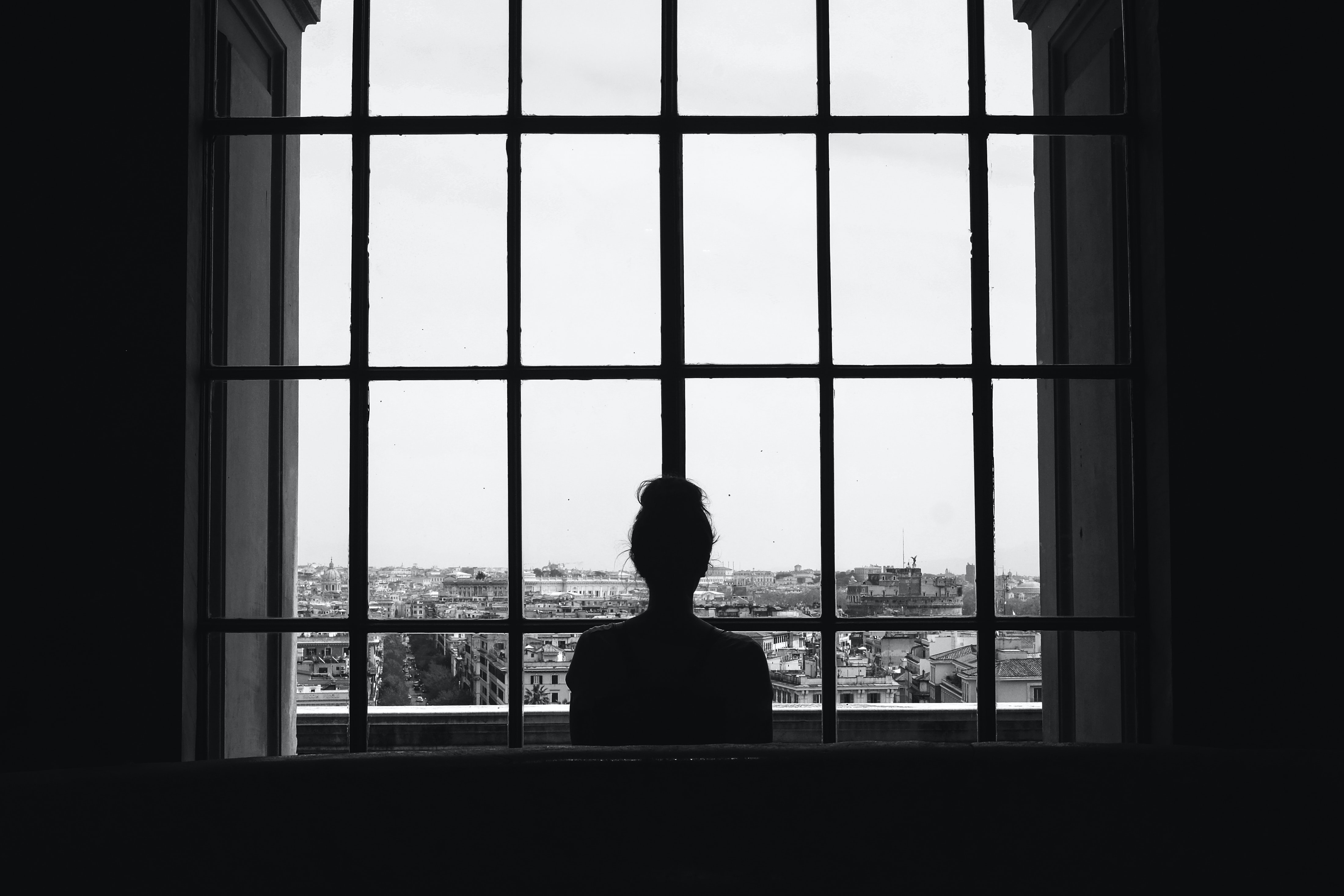 woman standing in front glass window