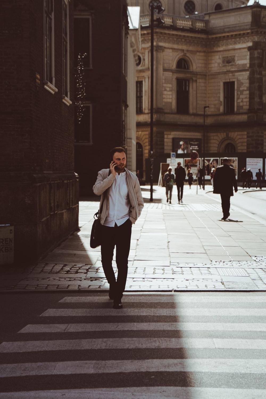 man holding phone while standing on pedestrian lane