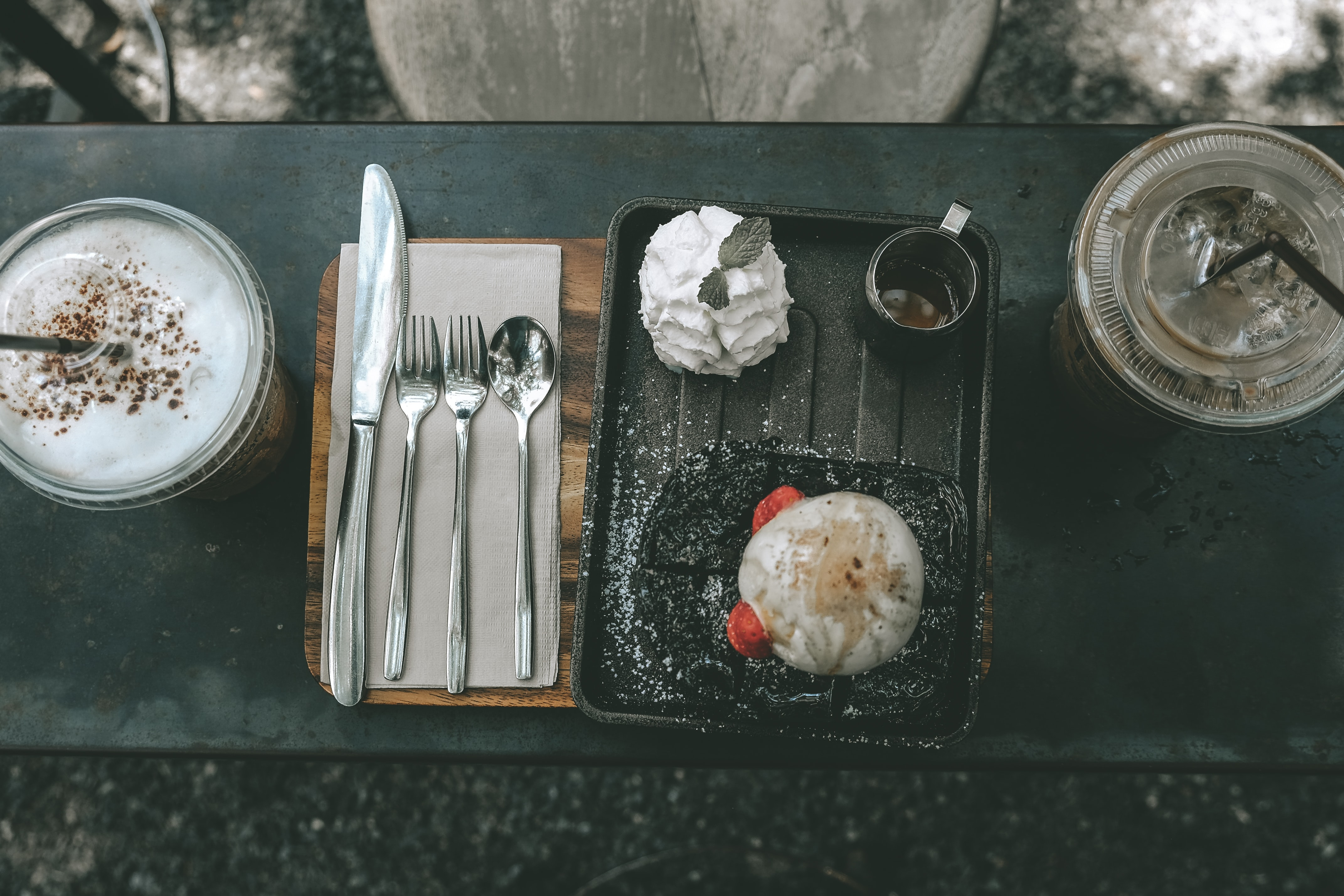 flat-lay photography of frappe cup beside cutlery and platter