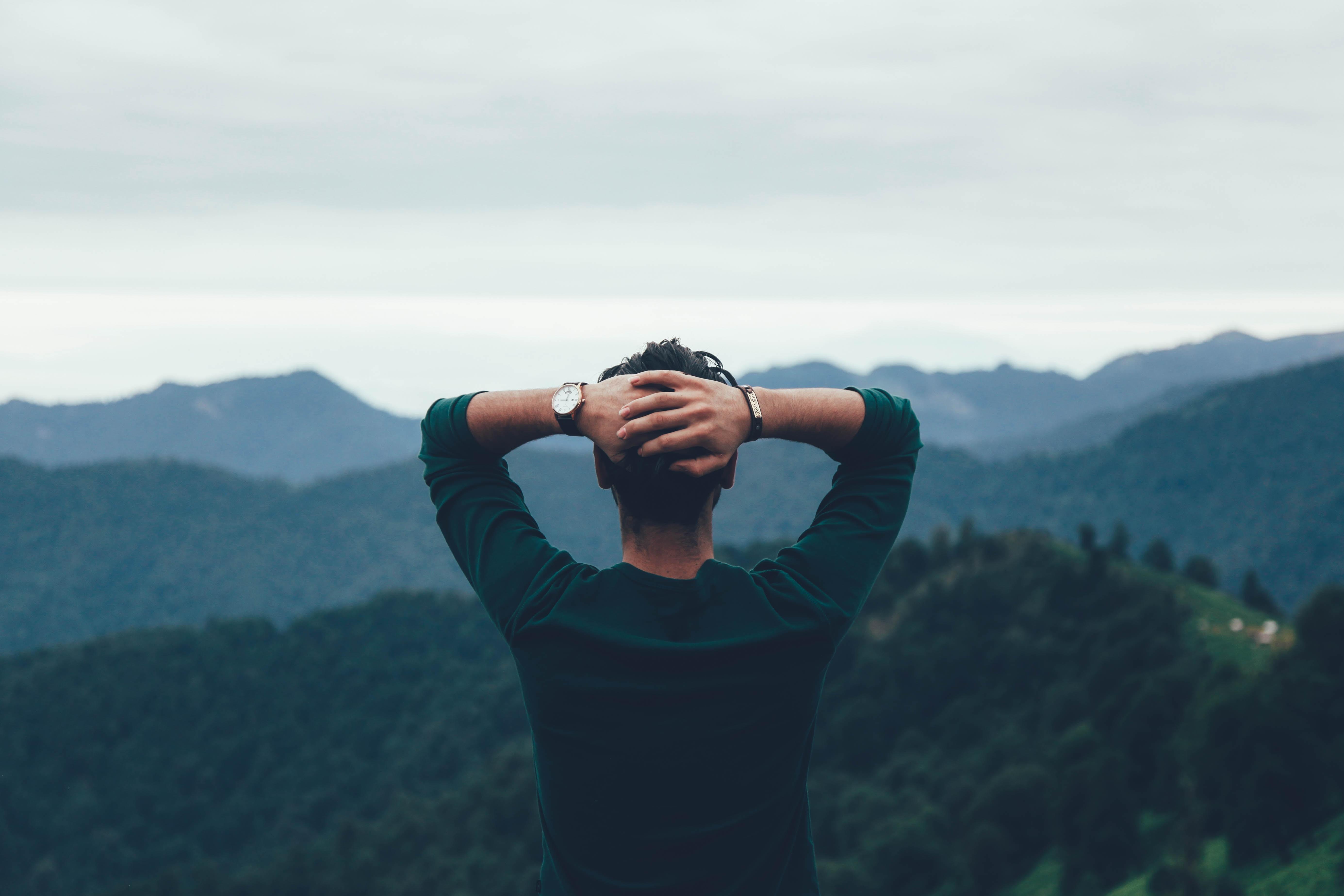 man wearing green raglan watching the mountain