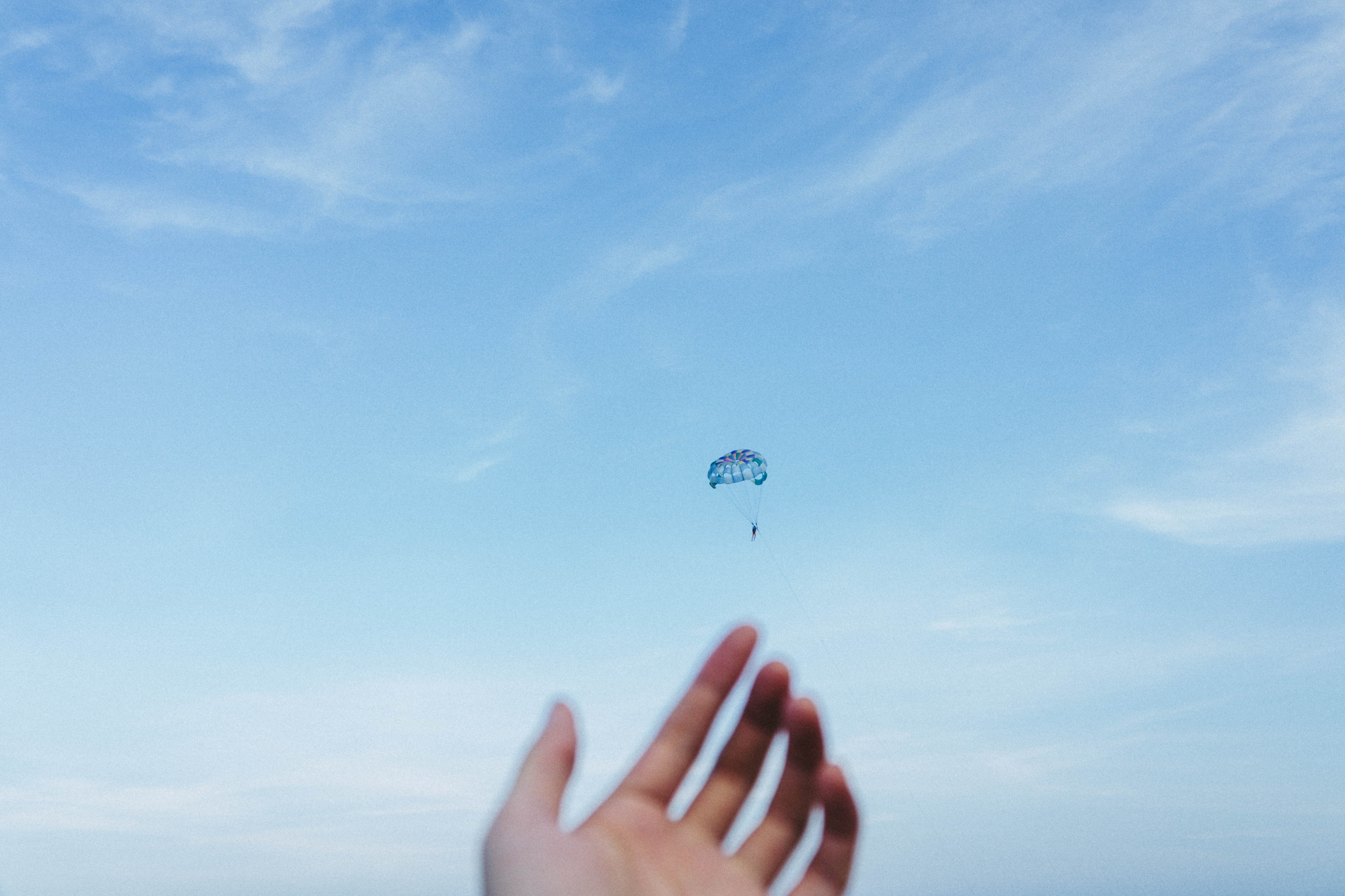 person riding parachute at daytime