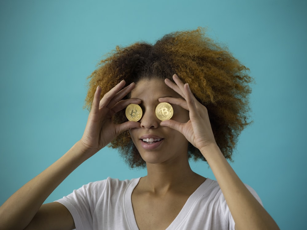 woman holding two round gold-colored coins