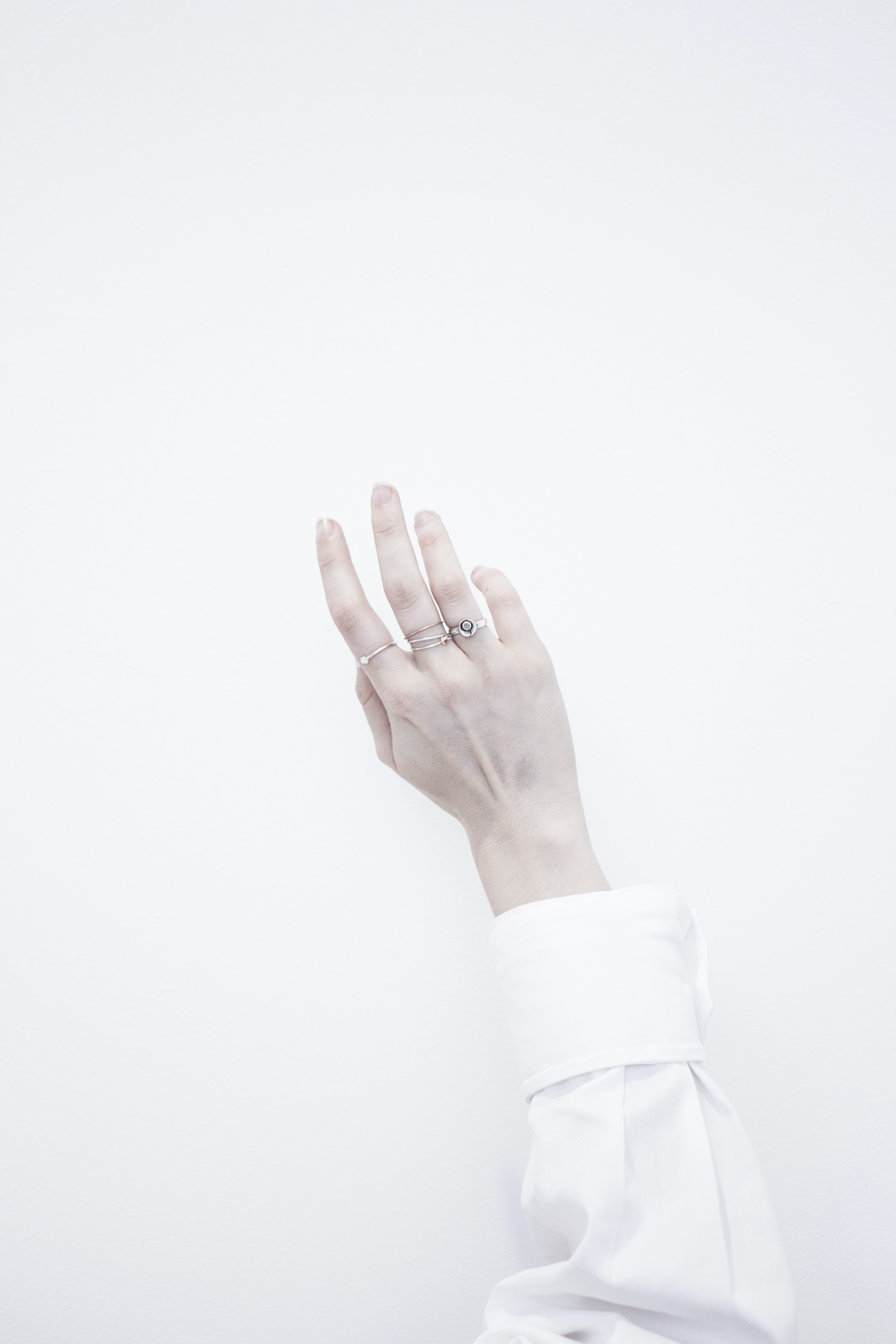 person's wearing several silver-colored rings