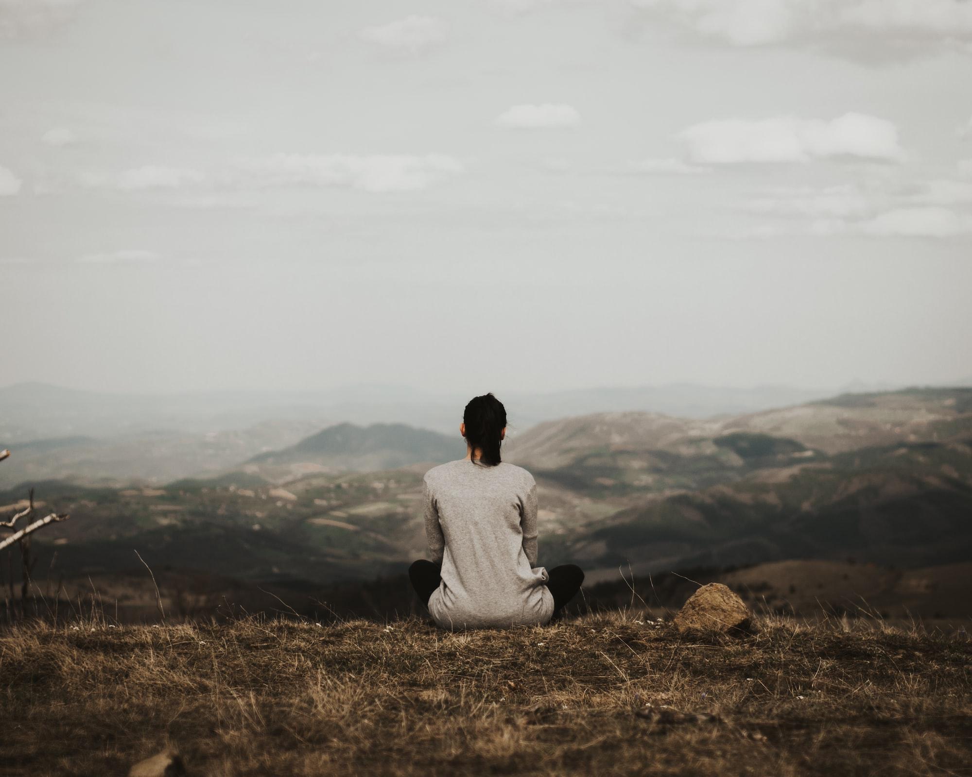 Une femme de dos en pleine méditation devant un paysage montagneux