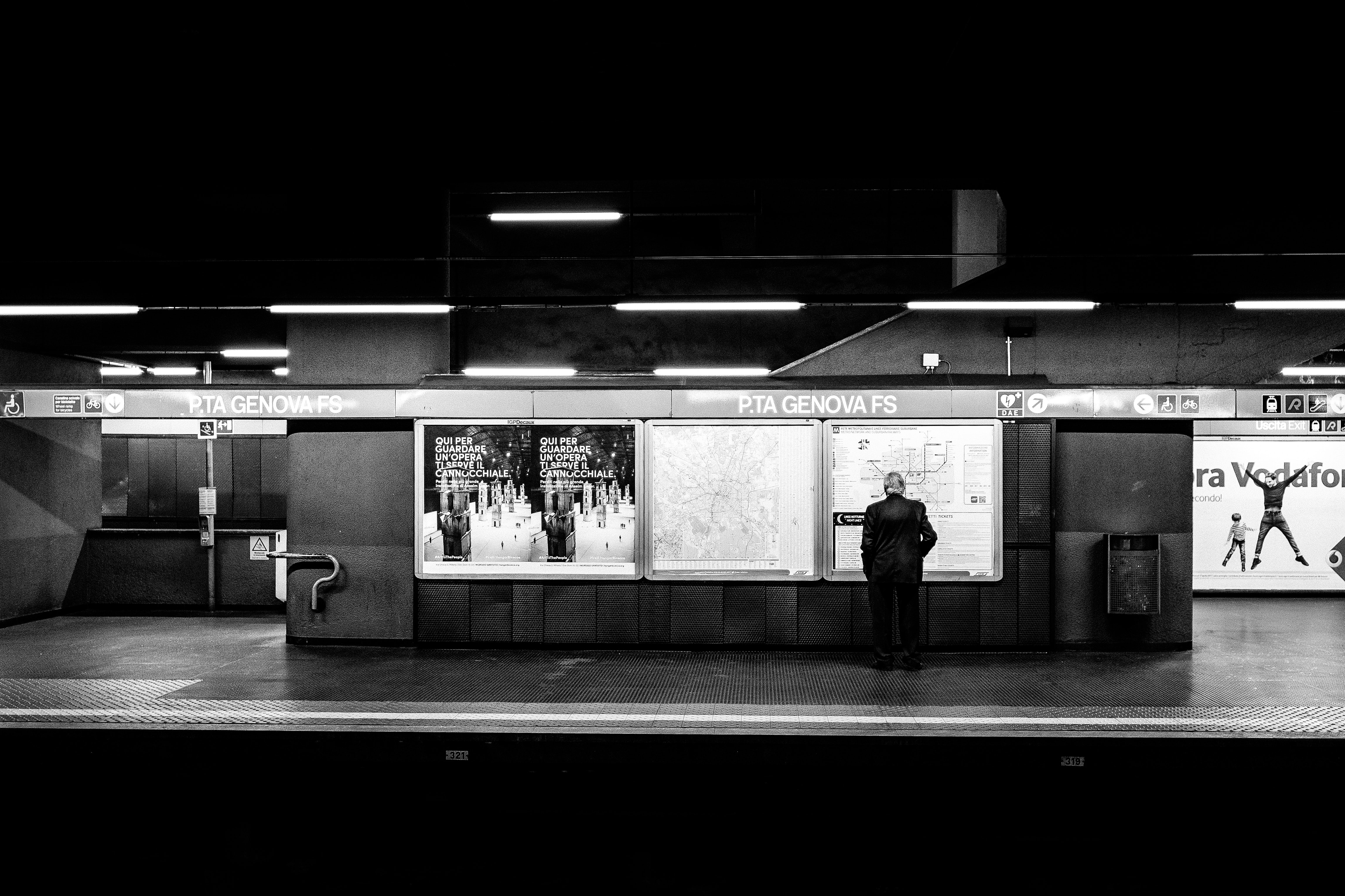 grayscale photo of man waiting on train station