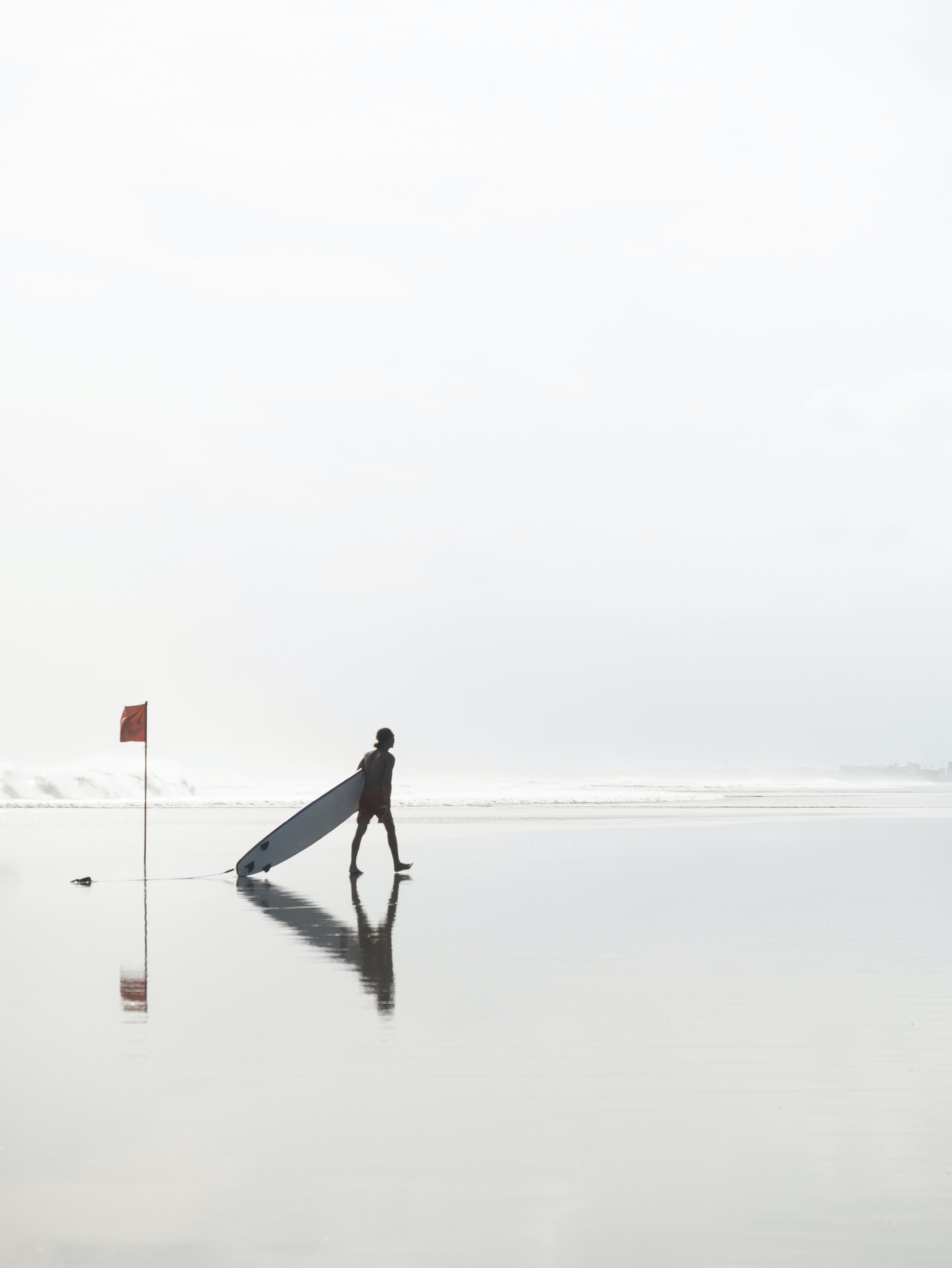 man walking while dragging surfboard at the beach near flag during day