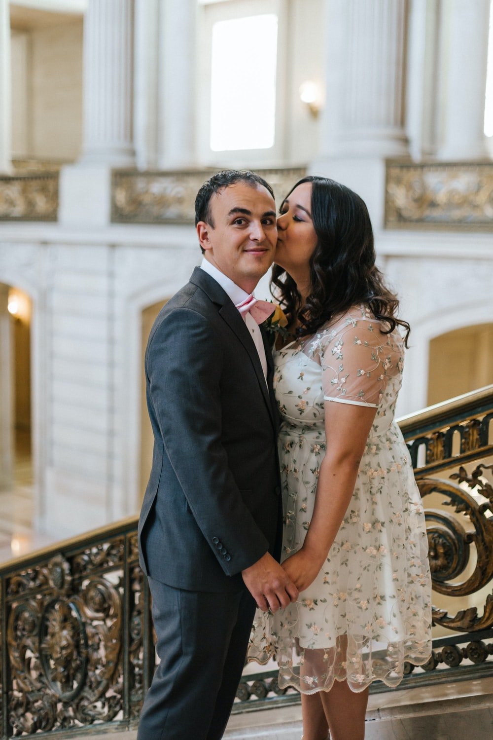 woman kissing man on cheek while standing on stair