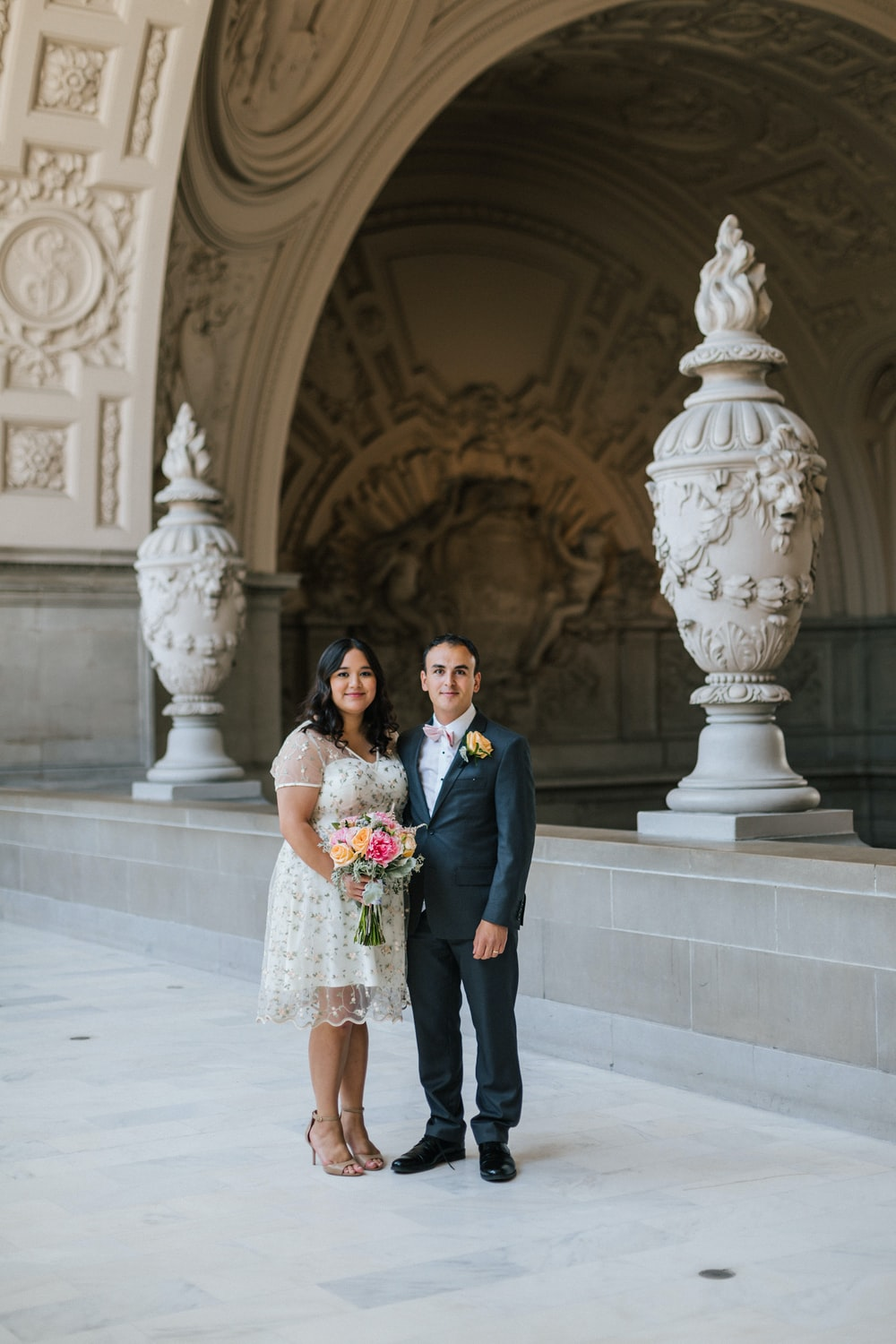 couple standing near gray concrete cathedral entrance