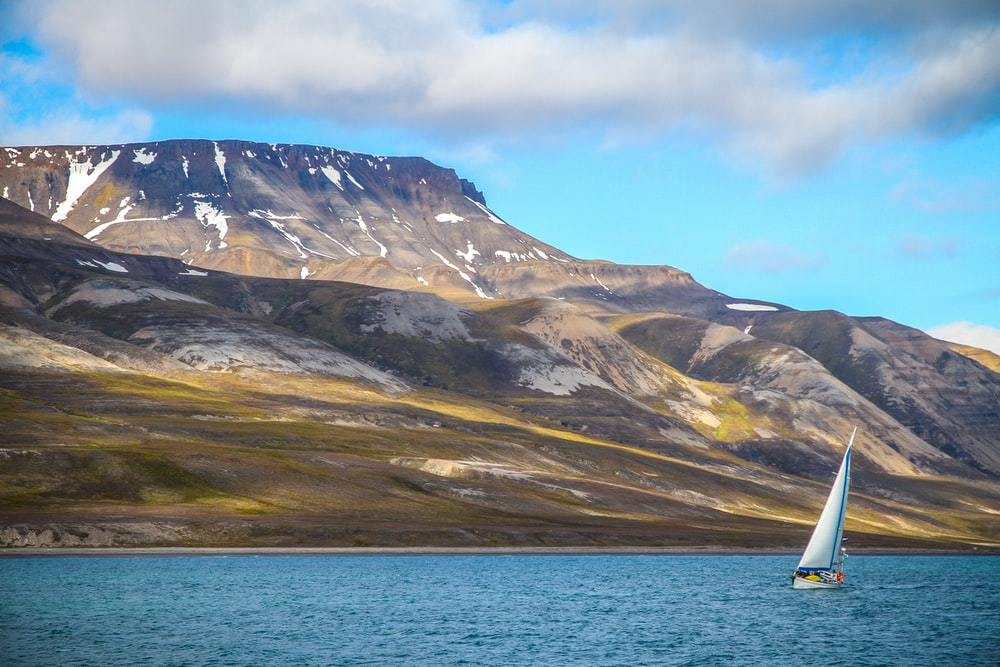 sailing boat on ocean with snow-capped mountain at distance