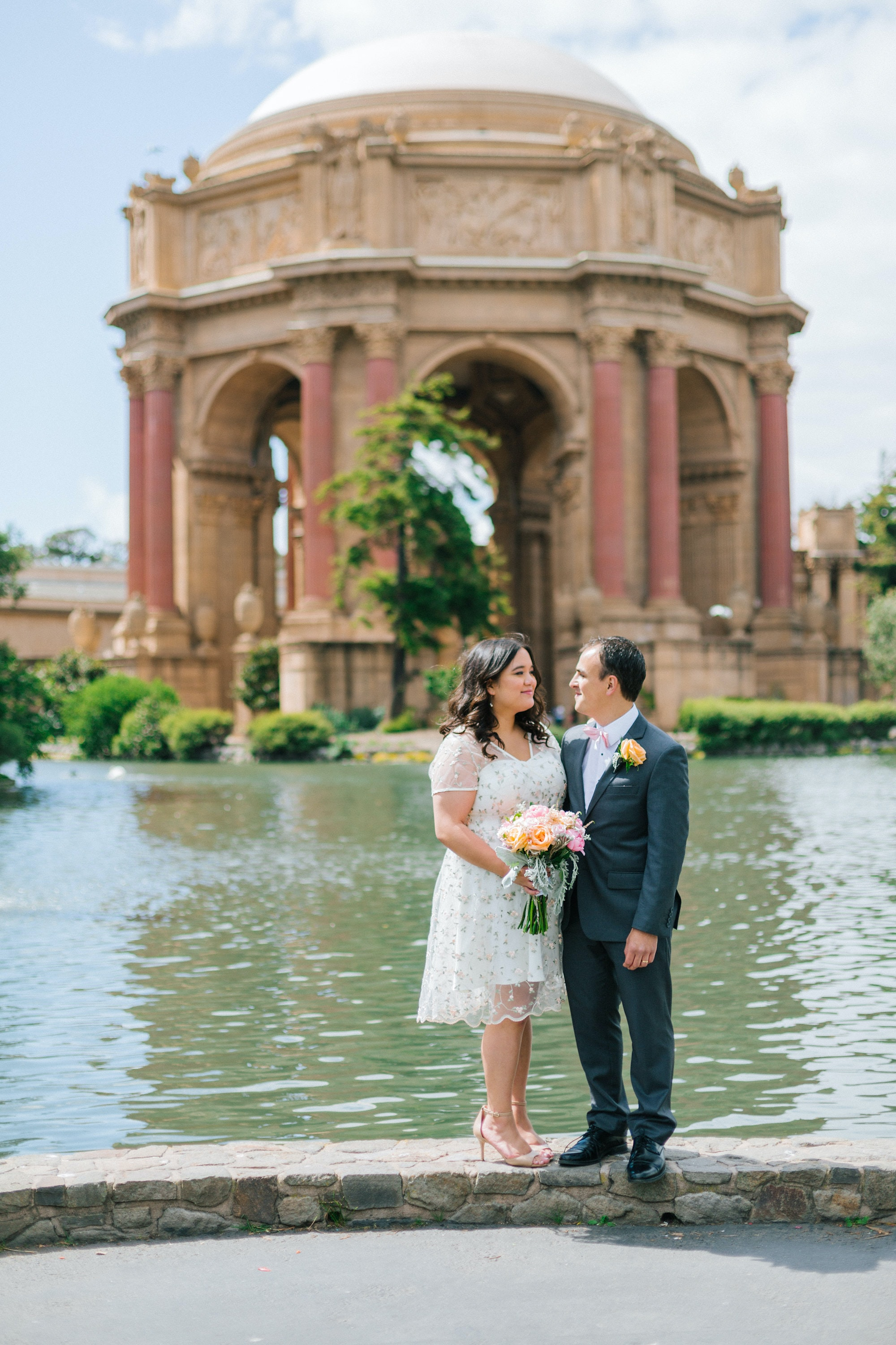 wedding couple standing on concrete ground beside body of water