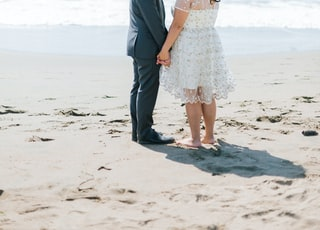 man and woman walking beside body of water