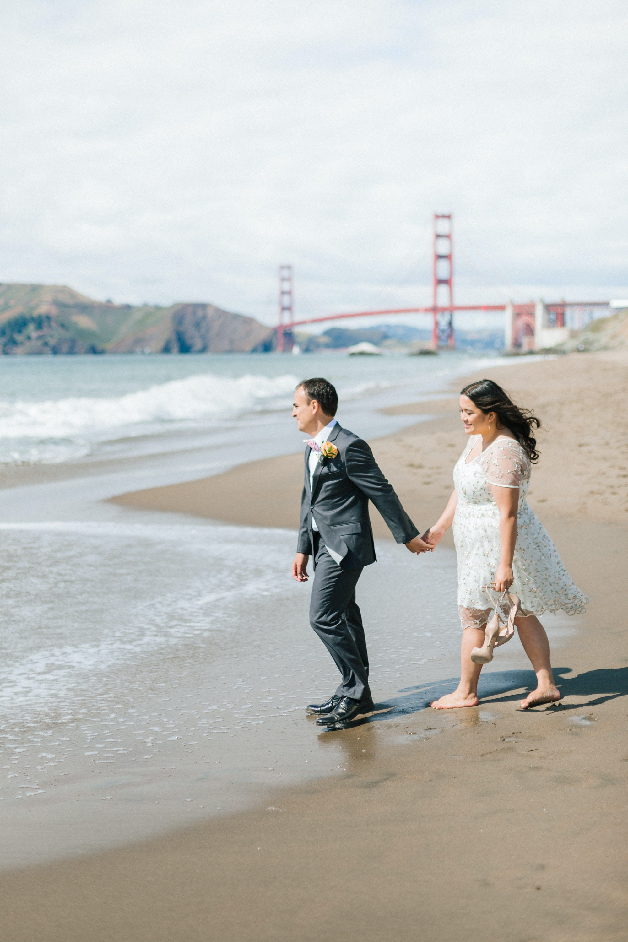couple walking on seashore near Golden Gate Bridge, San Francisco