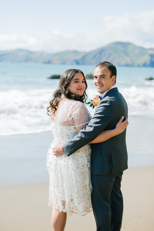 groom and bride standing on seashore