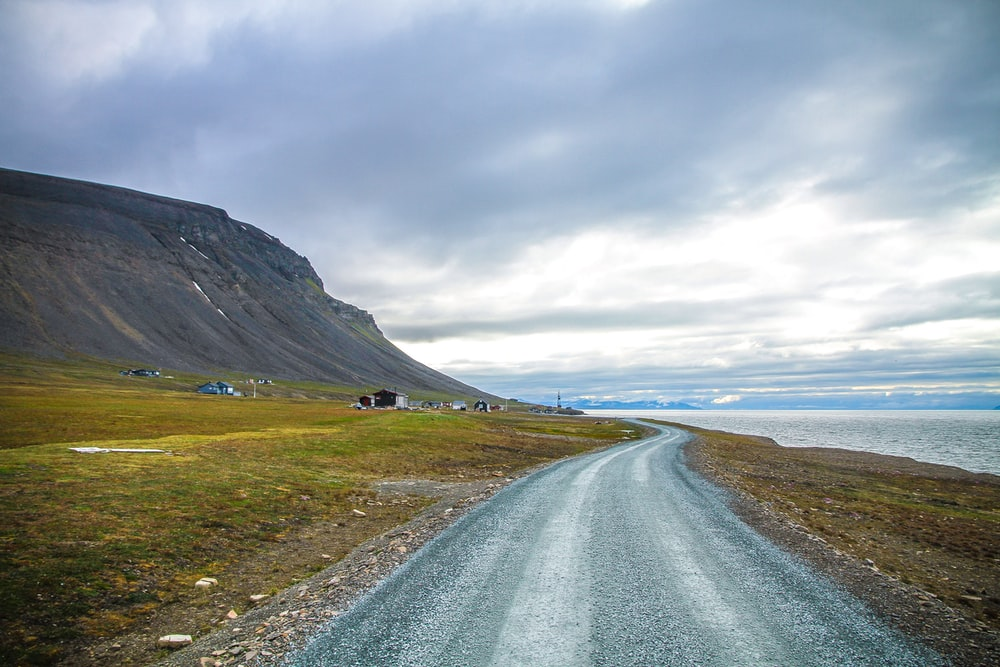 winding road near mountain range and body of water under nimbus clouds