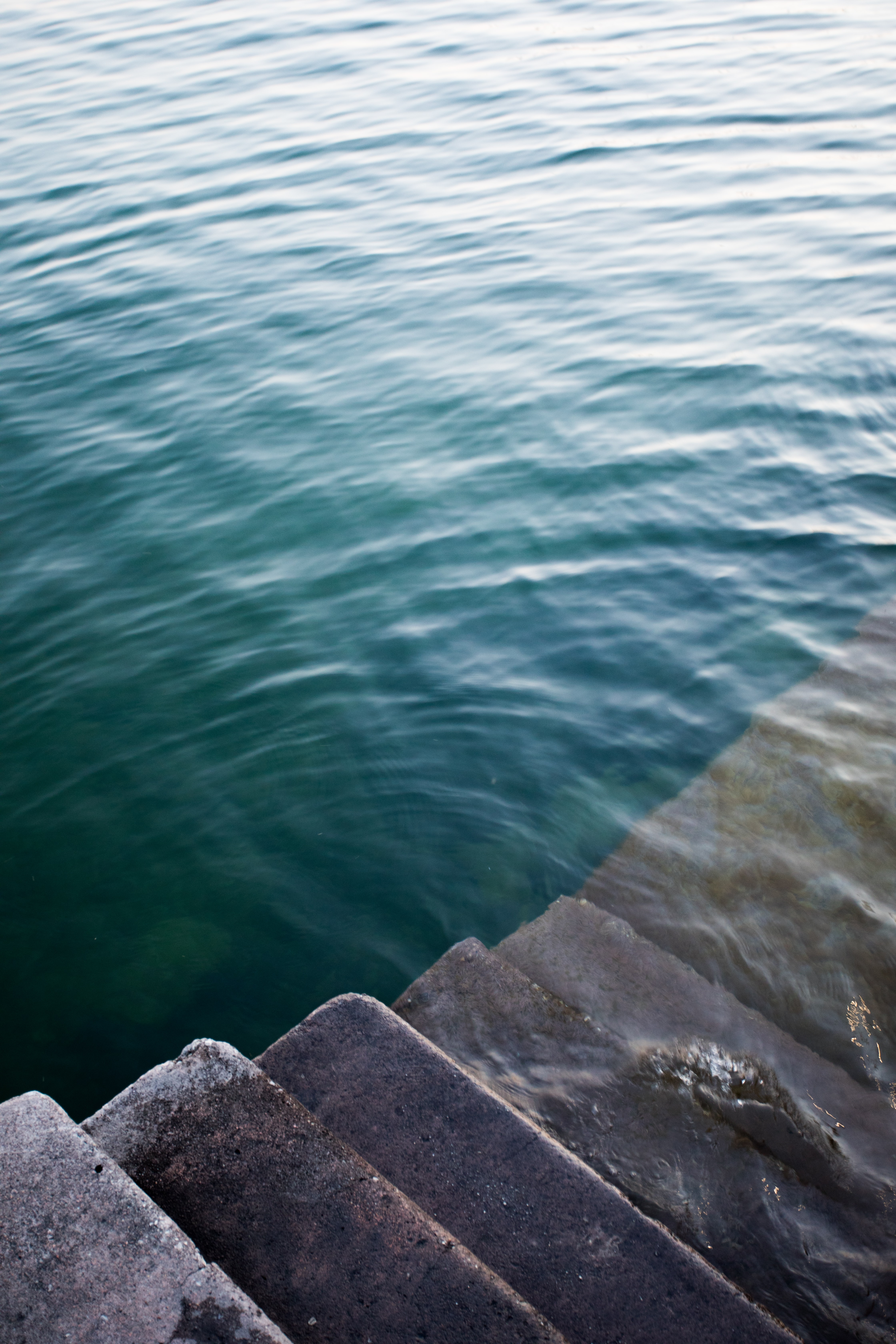 gray concrete stair in body of water