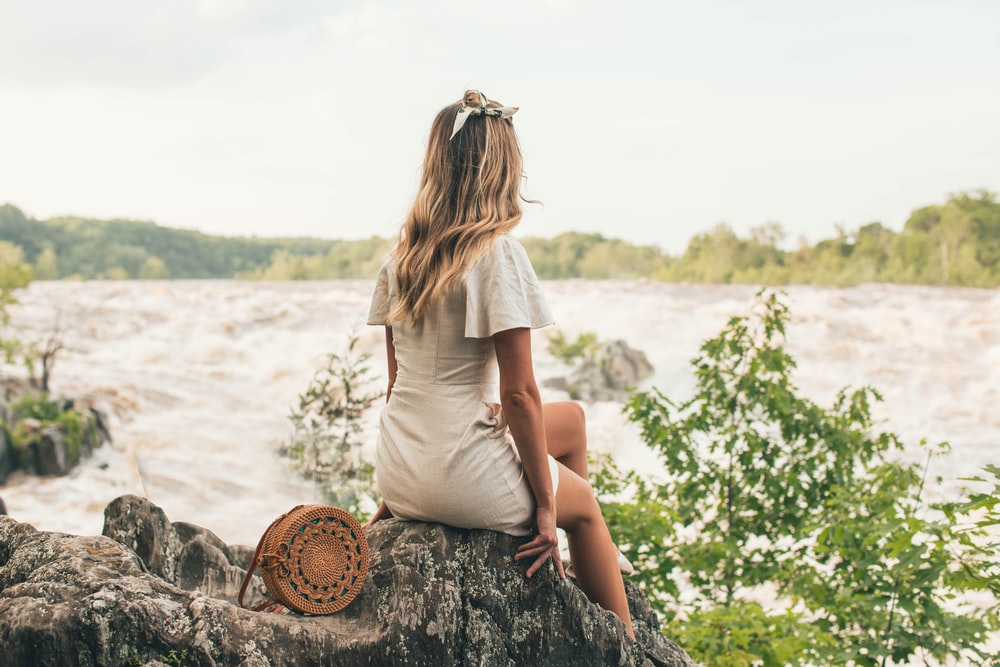 woman sitting on rock beside body of water