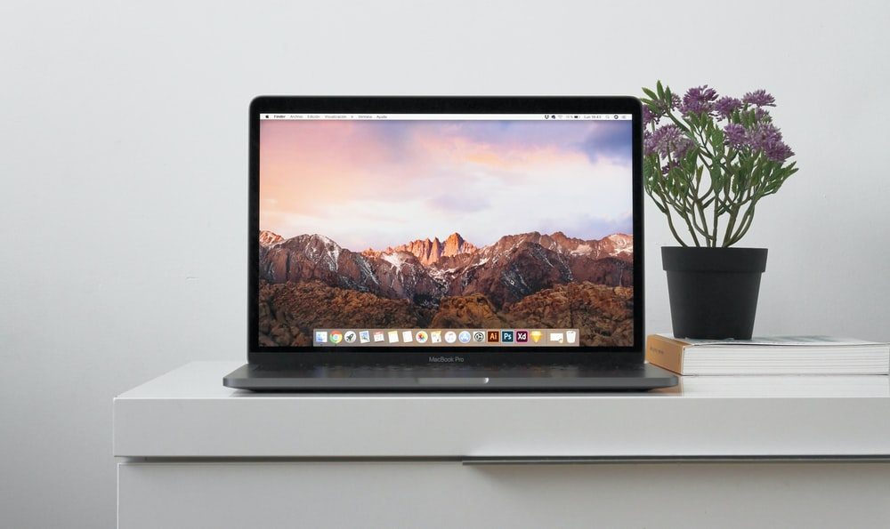 MacBook on top white table