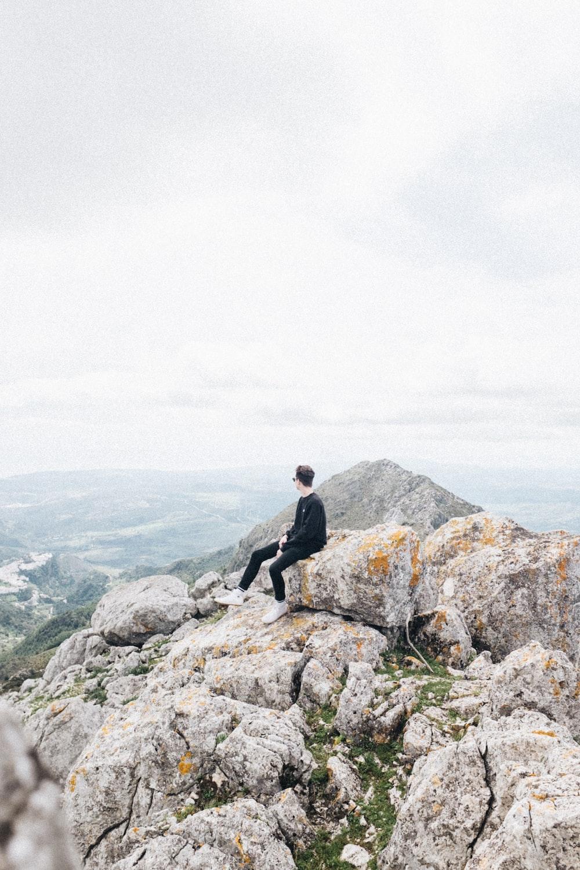 man sitting on rock at top of mountain