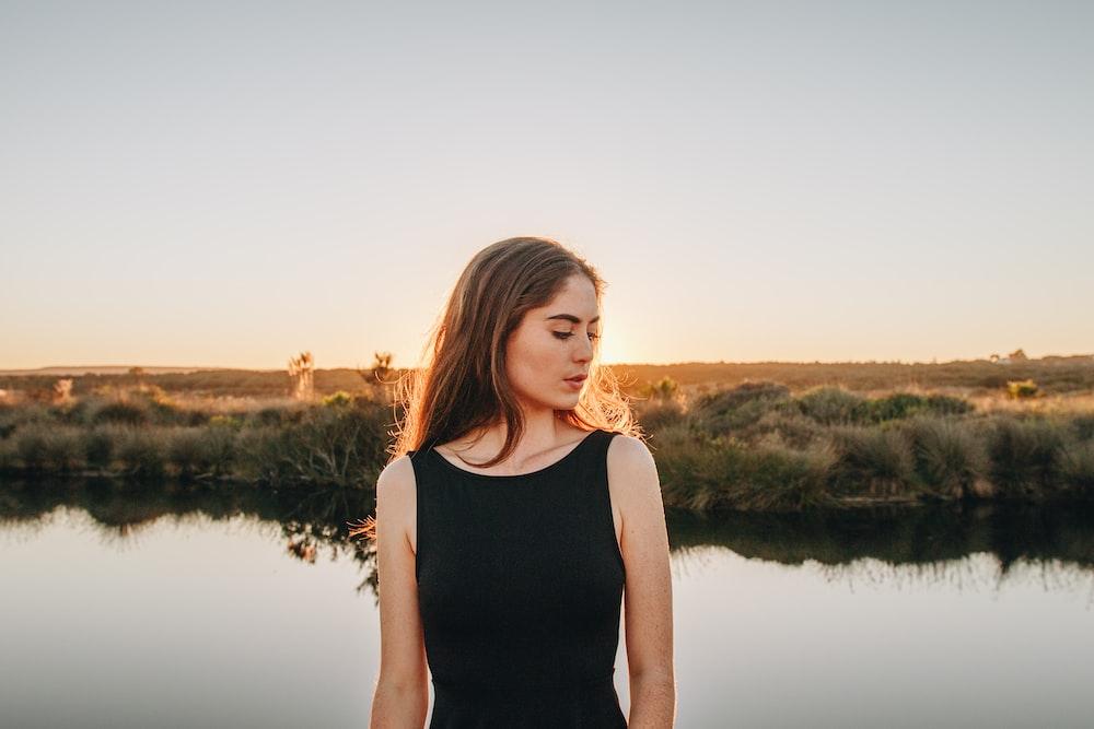 woman standing near pond