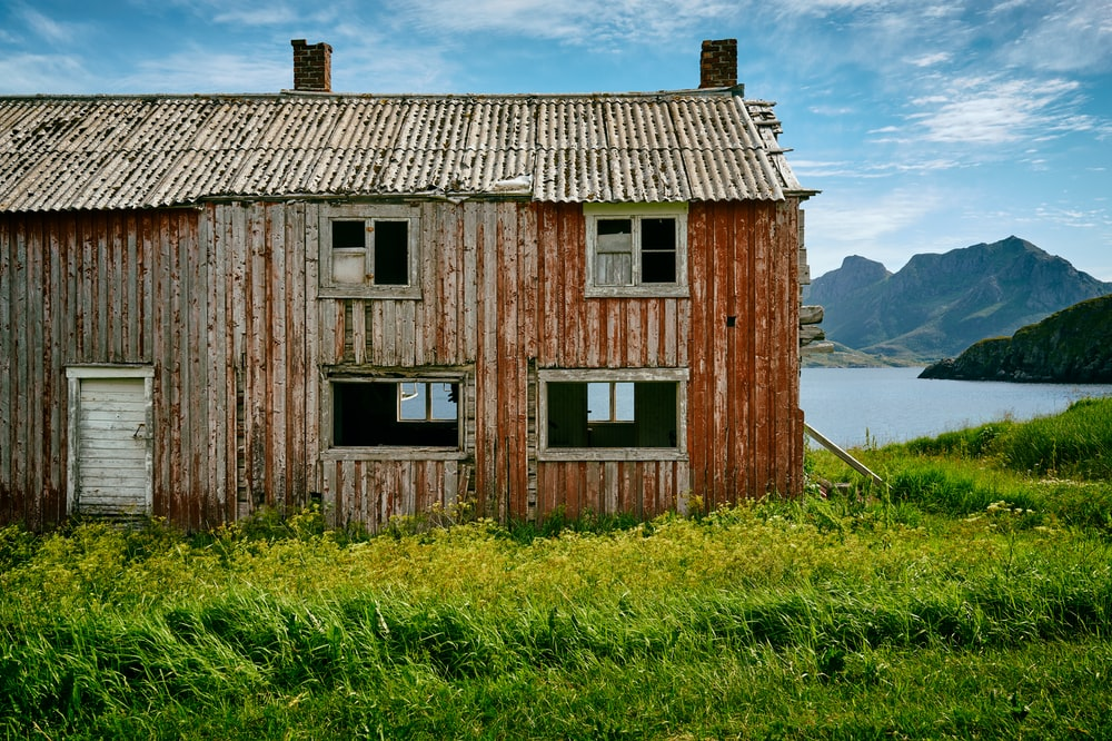brown wooden 2-storey house in front of a body of water