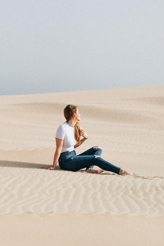 woman sitting on desert at daytime