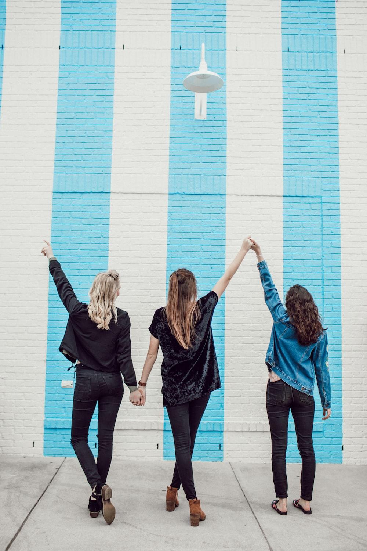 three woman holding hands white walking
