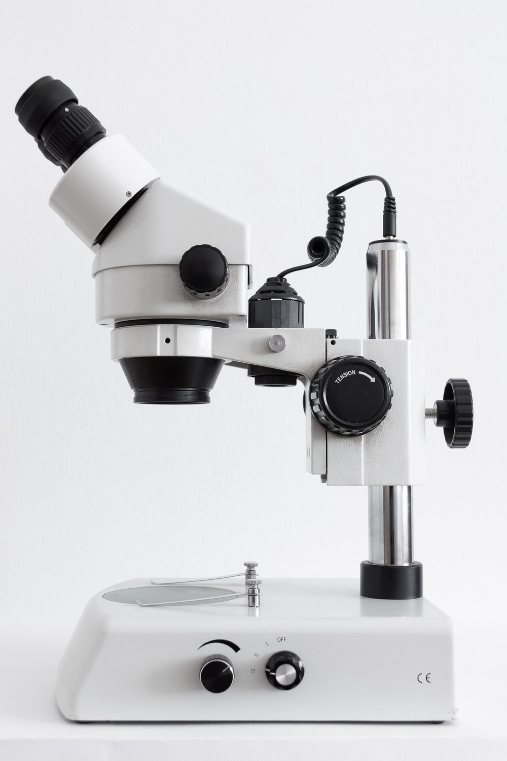 white and black microscope on white surface