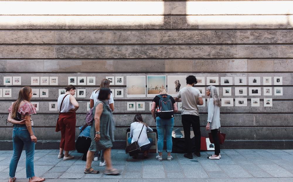people beside brown wall