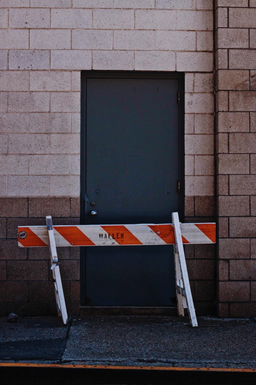 white and orange wooden fence beside black door