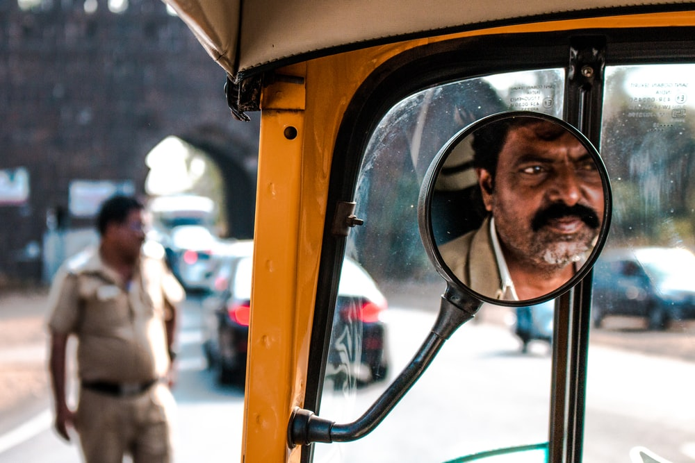driver's face reflecting on mirror