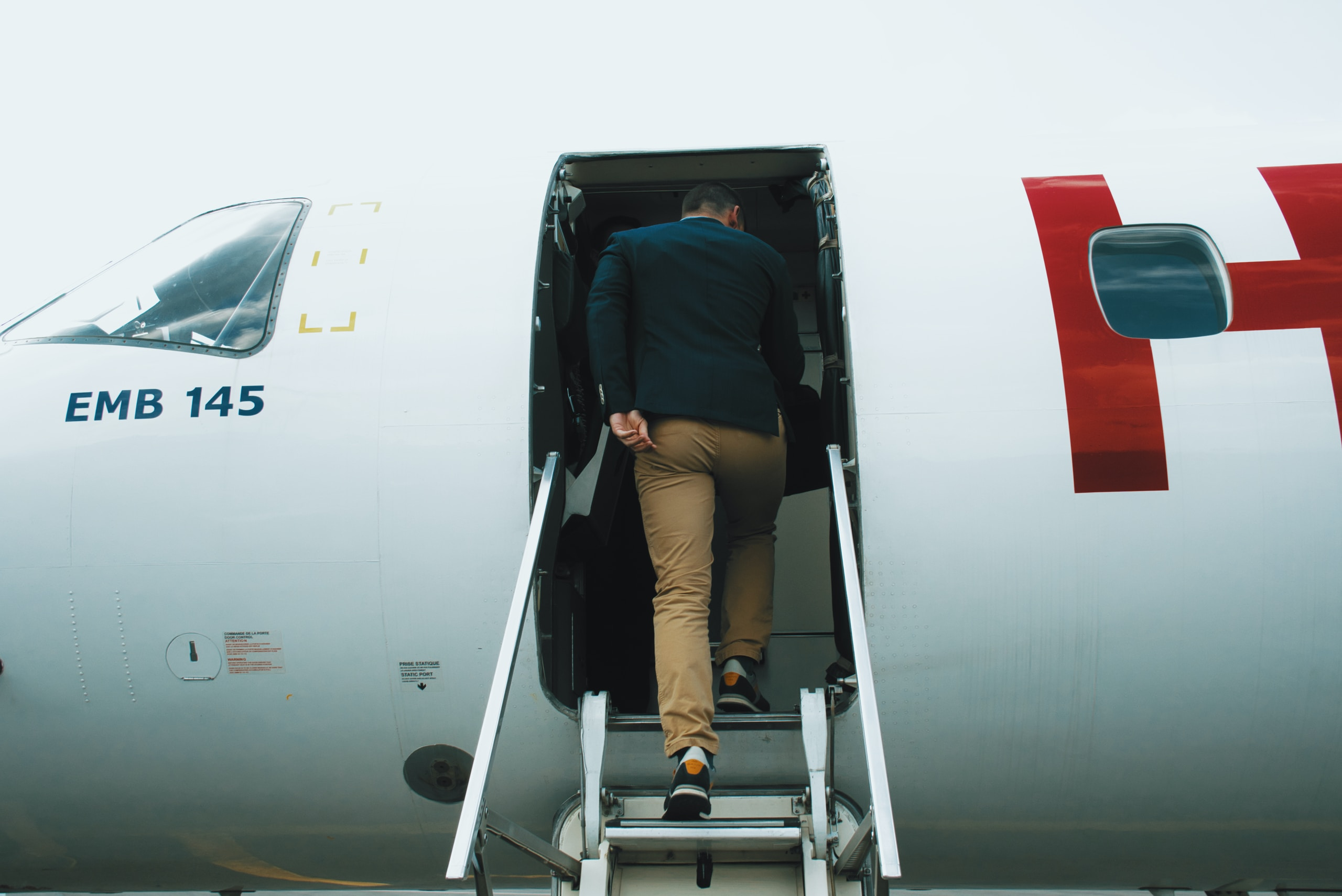 man entering plane during daytime