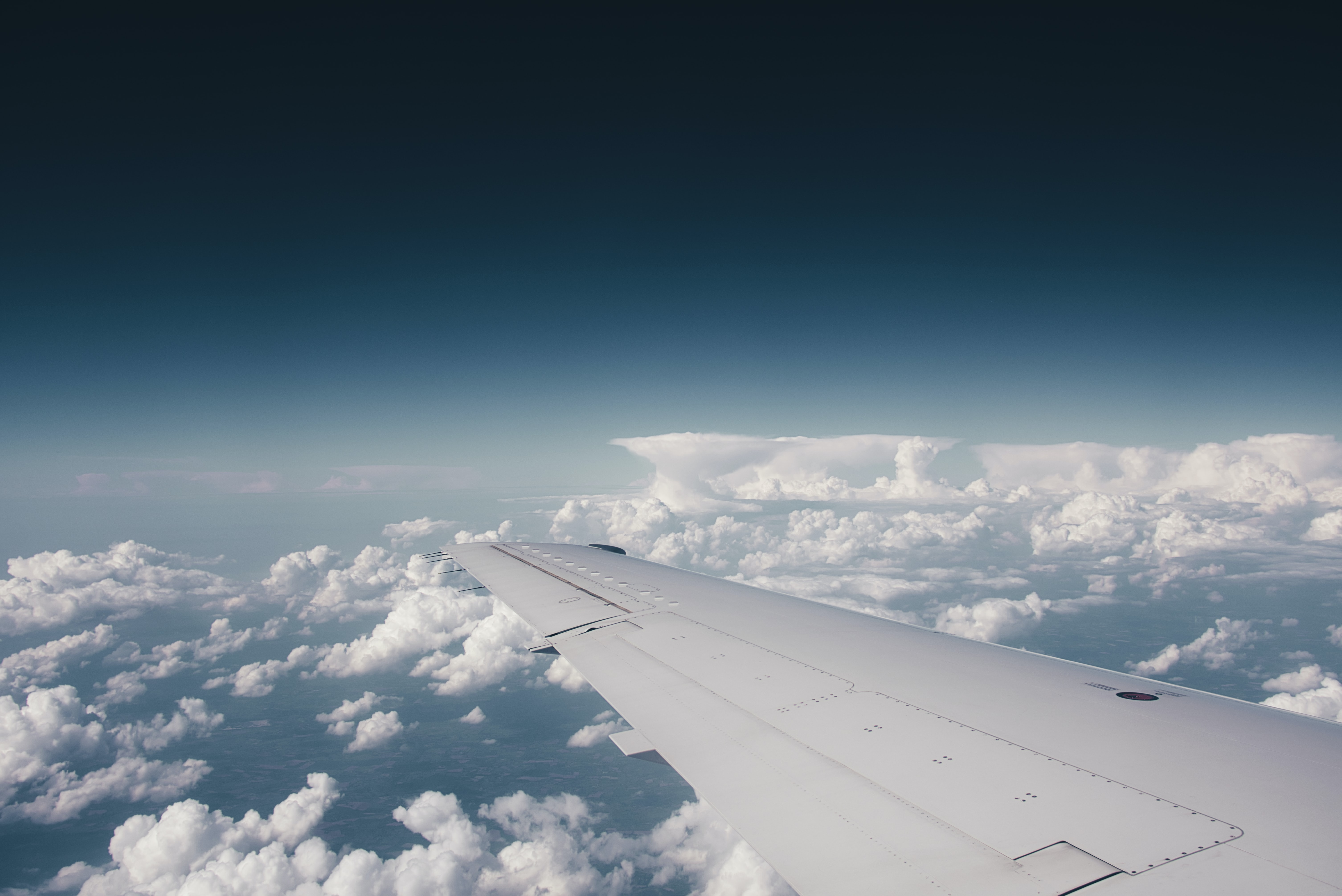 white plane wing above white clouds